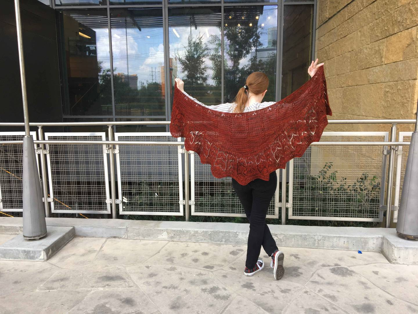 woman holding dark red crescent-shaped shawl suspended between her hands, and standing in front of railing at Austin Public Library