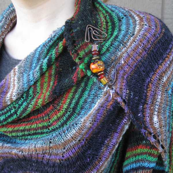closeup of larger Rosita shawl to illustrate twisted stitch closed lace texture, also features copper shawl pin with large hand-blown glass beads